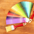 Paint brushes and bright palette of colors on wooden background - Stockfoto