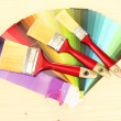 Paint brushes and bright palette of colors on wooden background - Foto Stock