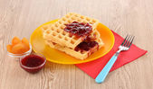 Tasty waffles with jam on plate on wooden background — Fotografia Stock