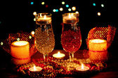 Amazing composition of candles and glasses on wooden table on bright background — Stock Photo