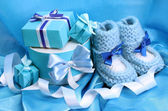 Beautiful gifts and baby's bootees on blue silk — Stock Photo