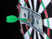 Dollar on bulls eye. Darts close-up on black background — Stock Photo
