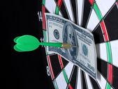 Dollar on bulls eye. Darts close-up on black background — Stock Photo