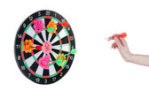 A hand throwing a dart at a sticker on darts on white background — Stock Photo
