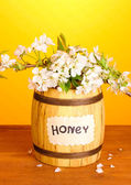 Sweet honey in barrel with blossoming branch on wooden table on yellow background — Stock Photo