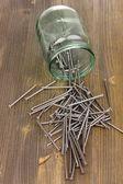 Clavos metálicos y jarra de vidrio en el fondo de madera — Foto de Stock