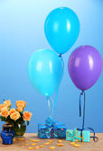 Romantic gift boyfriend. Colorful balloons holding a gifts on blue background — Stock Photo