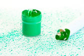 Jar with green gouache and tube with green watercolor on background of green spray close-up — Stock Photo