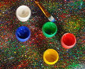 Jars with colorful gouache and brush on black background, spattered with colorful paint close-up — Stock Photo