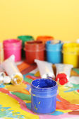 Tubes with colorful watercolor and jars with gouache on colorful picture close-up — Stock Photo
