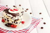 Sweet cake with chocolate on plate on wooden table — Stock Photo