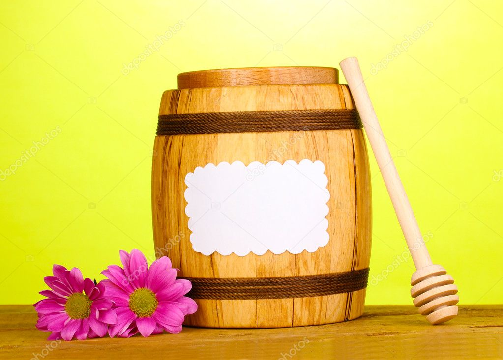 Sweet honey in barrel with drizzler on wooden table on green background — Stock Photo #11027528