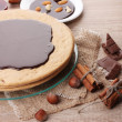 Stock Photo: Cake on glass stand and nuts on wooden table