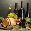 Royalty-Free Stock Photo: Barrel, bottles and glasses of wine and ripe grapes on wooden table on grey background