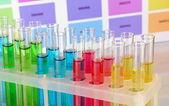 Reagenzgläser mit flüssigkeit farbe auf farbe muster hintergrund — Stockfoto