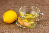 Healthy ginger tea with lemon on sackcloth — Stock Photo