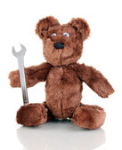 Sitting bear toy with wrench isolated on white — Stock Photo