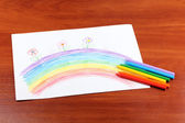 Children's drawing of rainbow and pencils on wooden background — Stock Photo