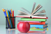 Composition of books, stationery and an apple on bright colorful background — Stock Photo