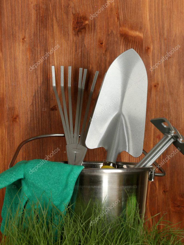 Garden tools on grass on wooden background close-up  Stock Photo #11038057