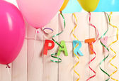 Party. Balloons against a wooden fence on blue background — Stock Photo
