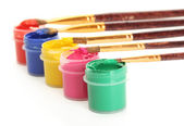 Brushes on the jars with colorful gouache on white background close-up — Stock Photo