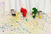 Renkli splash arka plan yakın çekim üzerinde renkli suluboya ile tüpler — Stok fotoğraf