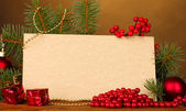 Blank postcard, Christmas balls and fir-tree on wooden table on brown background — Stockfoto