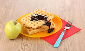 Tasty waffles with chocolate on plate on wooden background — Fotografia Stock
