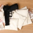 Cocaine and marihuana in packages and handgun on wooden background — Stock Photo