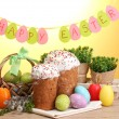 Beautiful Easter cakes, colorful eggs in basket and candles on wooden table on yellow background — Stock Photo #11071072