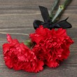 Stock Photo: Carnations and black ribbon on grey wooden background