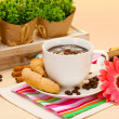 Cup of coffee and gerbera beans, cinnamon sticks on wooden table — Stock Photo #11071278