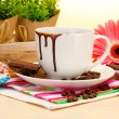 Dirty cup of coffee and gerbera beans, cinnamon sticks on wooden table — Stock Photo