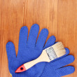 Brush and gloves on wooden background — Stock Photo #11071347