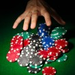 Poker chips and hand above it on green table — Stock Photo