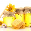Sweet honey in jars with honeycomb, wooden drizzler and flowers isolated on white — Stock Photo #11071884