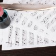 Musical notes and feather on wooden table — Stock Photo