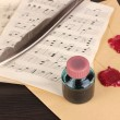Musical notes and feather on wooden table — Stockfoto