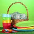 Bright plastic disposable tableware and picnic basket on the lawn on colorful background — Stock Photo #11072071