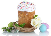 Beautiful Easter cake in basket, colorful eggs and flowers isolated on white — Stock Photo