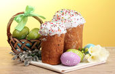 Beautiful Easter cakes, colorful eggs in basket and pussy-willow twigs on wooden table on yellow background — Stock Photo