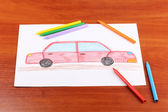 Children's drawing of red car and pencils on wooden background — Stock Photo