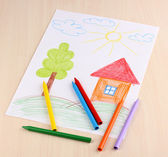 Children's drawing of house and pencils on wooden background — Zdjęcie stockowe
