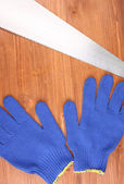 Saw and gloves on wooden background — Stock Photo