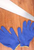 Saw en handschoenen aan houten achtergrond — Stockfoto