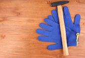 Hamer en handschoenen aan houten achtergrond — Stockfoto