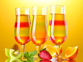 Jalea de fruta en vasos y frutas sobre fondo amarillo — Foto de Stock