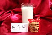 赤い布の背景上の cookie とミルクのガラス — ストック写真