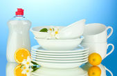 Empty clean plates and cups with dishwashing liquid and lemon on blue background — ストック写真
